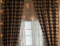 Cortinas de Brown con las guirnaldas para la Navidad Imagen de archivo