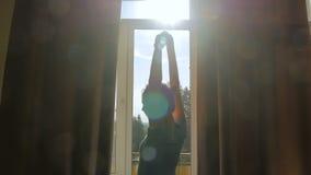 Cortinas de janela da abertura da mulher