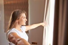 Cortinas de la ventana y de abertura del dormitorio de la mujer que hacen una pausa fotografía de archivo