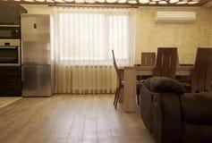 Cortinas de lujo en la ventana Sala de estar moderna con un pedazo de cocina y de mesa de comedor foto de archivo libre de regalías