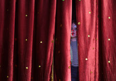 Cortinas de Peering Through Stage do palhaço do menino Imagens de Stock Royalty Free