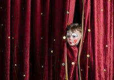 Cortinas de Peering Through Stage do palhaço do menino Fotografia de Stock Royalty Free