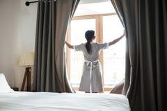 Cortinas de ventana femeninas de abertura de la camarera en la habitación imágenes de archivo libres de regalías