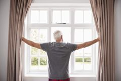 Cortinas do quarto da abertura do homem superior e vista fora da janela fotos de stock royalty free