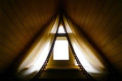 Cortinas hermosas en ventana del ático debajo del tejado imagen de archivo