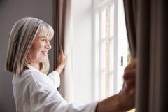 Cortinas superiores do quarto da abertura da mulher e vista fora da janela fotografia de stock royalty free