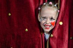 Cortinas vestindo de Makeup Peeking Through do palhaço da menina Fotos de Stock Royalty Free