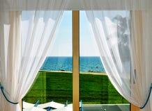 Cortinas y ventana blancas con la opinión del mar Imagenes de archivo