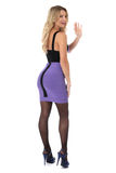 Cortocircuito apretado Mini Dress de la púrpura de la mujer que lleva que agita joven con las medias y los zapatos del tacón alto Imagen de archivo libre de regalías