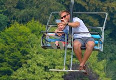 Man taking selfie with little boy while riding on a chair lift. Stock Images