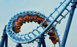 Roller coaster ride filled with thrill seekers doing corkscrew. Royalty Free Stock Photo