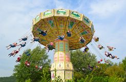 The Wave Swinger  Chair o plain carousel  people on swinging seats on chains. Royalty Free Stock Images