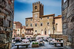 Cortona Communal Palace. With renaissance tower clock seen from a narrow street in the historic center, an old medieval town in Tuscany Royalty Free Stock Photography