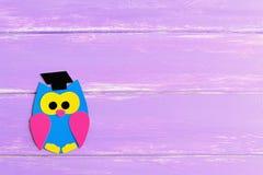 Coruja colorida do cartão em um fundo de madeira lilás com lugar vazio para o texto Coruja brilhante feita do cartão colorido imagens de stock royalty free