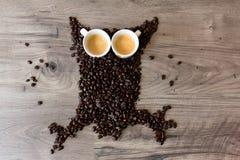 A coruja deu forma à figura feita fora dos feijões de café e de dois copos completos do café sobre uma tabela Imagem de Stock Royalty Free