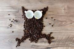 A coruja deu forma à figura feita fora dos feijões de café e de dois copos vazios do café sobre uma tabela Foto de Stock