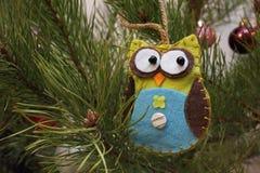 Coruja do brinquedo de feltro em uma árvore de Natal verde Fotos de Stock