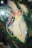 Coruja pequena quilled do brilho que pendura em um ramo spruce Foto de Stock