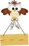 Coruja que guarda o sinal de madeira Fotografia de Stock Royalty Free
