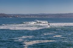 Coruna coastline. View from coastal coruna in Spain onto blue waters of Atlantic Ocean with white waves and houses Stock Photo