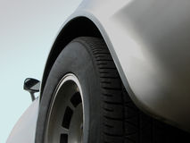 Corvette 3. The side view of the rear wheel on a silver Corvette, from the ground perspective, showing the curves, rim and style of the sports car Stock Photography