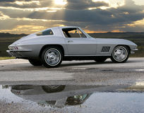 1967 Corvette coupe. This 1967 Chevrolet Corvette silver coupe sits under the sun breaking skies. Car reflecting in water after rain storm Royalty Free Stock Image