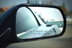 Corvette side mirror with the words, Objects in mirror are closer than they appear. Black outside with chrome and mirror stock photo
