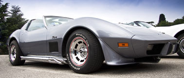 Corvette stingray. Grey Corvette stingray with chromed wheels on a paved parking Royalty Free Stock Photos