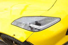 Corvette Z06 Supercar. Detail of a front lighthouse with rain droplets, front view of a yellow Chevrolet Corvette Z06. Car exterior details, parked on the street stock photography