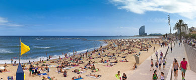 Corwded beach of Barceloneta - Barcelona. Crowded beach of Barceloneta with modern hotel 'W' in the background in summer time in BARCELONA, SPAIN - AUGUST 13 Stock Images