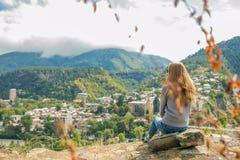 Così una bella donna sta stando sopra una montagna in una maglia con cappuccio esaminando le montagne e gli alberi da sopra Fotografie Stock