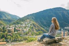 Così una bella donna sta stando sopra una montagna in una maglia con cappuccio esaminando le montagne e gli alberi da sopra Fotografia Stock Libera da Diritti