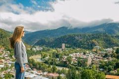 Così una bella donna sta stando sopra una montagna in una maglia con cappuccio esaminando le montagne e gli alberi da sopra Fotografia Stock
