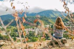 Così una bella donna sta stando sopra una montagna in una maglia con cappuccio esaminando le montagne e gli alberi da sopra Immagine Stock