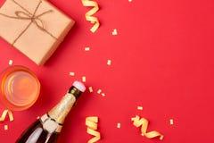 Cosas de la caja de regalo y de la fiesta de cumpleaños en un fondo rojo Foto de archivo libre de regalías