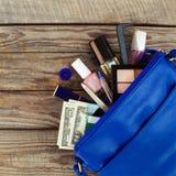 Cosas del bolso abierto de la señora el monedero de las mujeres en el fondo de madera Imágenes de archivo libres de regalías