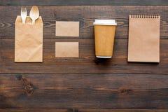 Cosas disponibles Bolsa de papel, vajilla, cuaderno en copyspace de madera de la opinión superior del fondo foto de archivo libre de regalías
