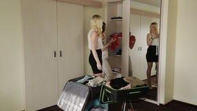 Cosas lindas del cambio de la novia fuera del armario en una maleta almacen de metraje de vídeo