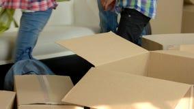 Cosas que embalan de la gente en las cajas almacen de metraje de vídeo