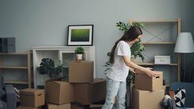 Cosas que llevan de la muchacha y del individuo en cajas durante la relocalización en el nuevo apartamento metrajes