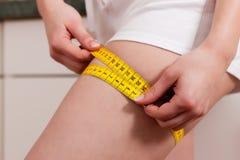 Coscia di misurazione della donna con nastro adesivo Fotografie Stock