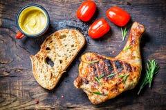 Coscia di pollo arrostita con pane tostato ed il pomodoro ciliegia Immagini Stock