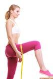 Coscie di misurazione della donna con la misura di nastro peso Fotografie Stock