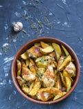 Coscie di pollo al forno del forno con le patate, le erbe e le spezie delle verdure nel piatto di cottura Fotografia Stock Libera da Diritti