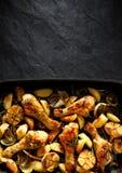 Coscie di pollo arrostite con i cunei della patata, l'aglio, la cipolla e le erbe aromatiche su una leccarda, vista superiore, fo Fotografia Stock