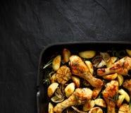 Coscie di pollo arrostite con i cunei della patata, l'aglio, la cipolla e le erbe aromatiche su una leccarda, vista superiore, fo Fotografia Stock Libera da Diritti