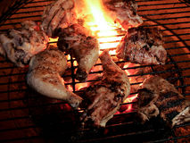 Coscie di pollo arrostite e coscie su una fiamma aperta Immagini Stock