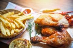 Coscie di pollo arrostite sul canestro di legno delle patate fritte e del tagliere con le spezie piccanti delle erbe dei peperonc fotografia stock libera da diritti