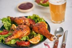 Coscie di pollo arrostite arrostite sulla griglia sul piatto scuro con salsa al pomodoro in ciotola e foglie della lattuga, tazza immagine stock libera da diritti