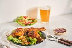 Coscie di pollo arrostite arrostite sulla griglia sul piatto scuro con salsa al pomodoro in ciotola e foglie della lattuga, tazza immagini stock libere da diritti